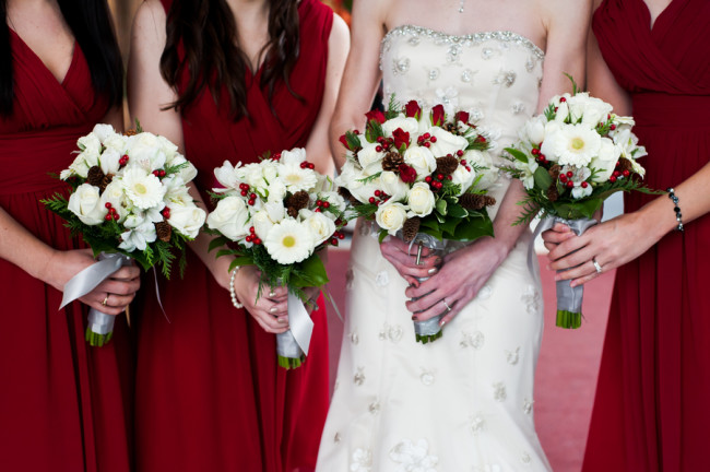 Bride standing with bridesmaids in red dresses holding white rose bouquet