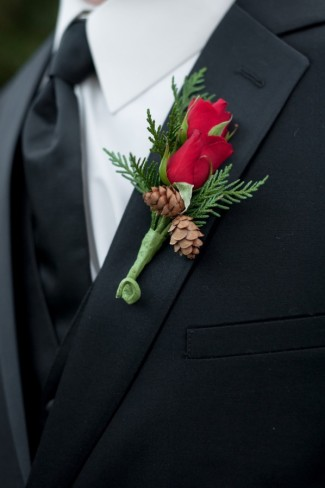Groom wearing a red rose boutonniere with pine cones and pine
