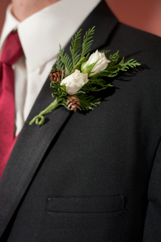 Groomsmen wearing a white rose boutonniere with pine cones and pine