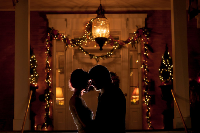Bride and groom head to head with Christmas light in the back ground