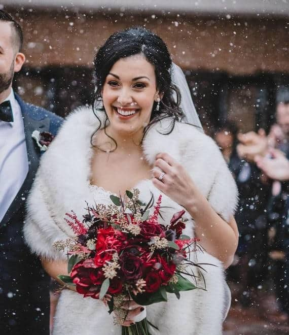 Bride wearing a faux fur wrap for winter wedding accessory