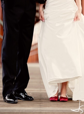 Bride and groom standing together with bride wearing red flats