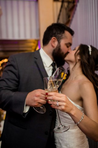 Bride and groom clinking champagne glasses and kissing captured by Stacy Anderson Photography