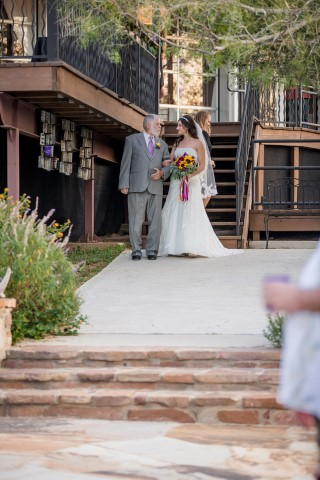 Bride walking with her father down the aisle at Terradorna carrying a bouquet of sunflowers
