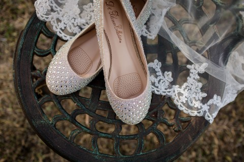 Silver ballet flats with rhinestones onto of a veil for bridal attire