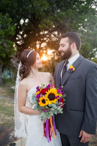 Bride carrying a sun flower bouquet with ribbons posing with her new husband