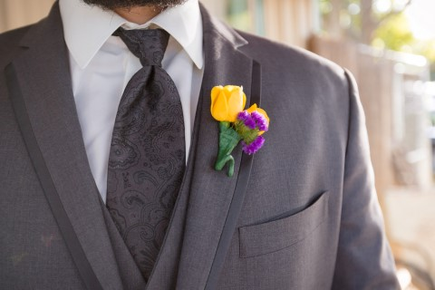 Groom wearing grey suit and paisley tie, yellow and purple boutonniere