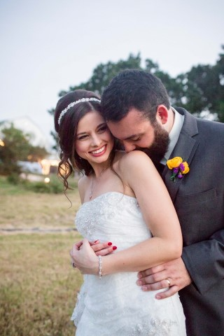 Groom embracing bride and kissing her shoulder captured by Stacy Anderson Photography