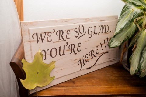 "A rustic fall themed wooden sign that says ""we're so glad you're here"" for wedding reception decor"
