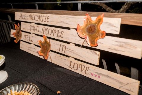 "planks of wood with ""all because two people fell in love"" painted on it"