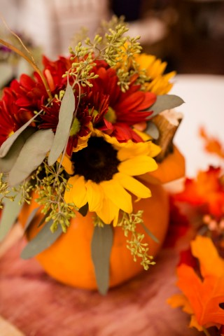 Pumpkin filled with flowers from HEB Blooms for fall wedding reception