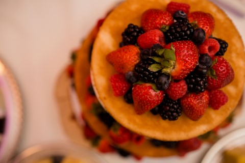 Naked cake with blackberries and strawberries on top created by Michelle's Patisserie for wedding