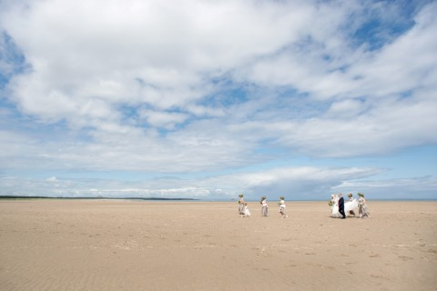 Bride walking to wedding ceremony along beach in Scotland with bridesmaids wearing grey dresses