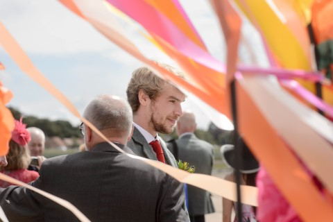 Groom during beach wedding ceremony in Scotland wearing a tux from McCalls Highland Wear
