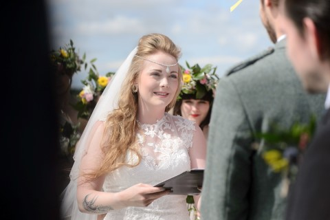 Bride during beach wedding ceremony wearing a gown from Victoria Kay Designer Rainbow