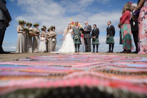 Bride and groom standing in front of all wedding guests during beach ceremony in Scotland