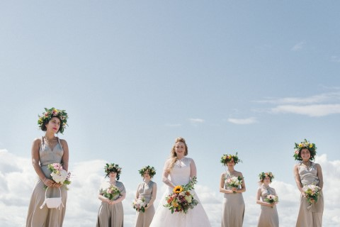 Bride standing on beach with bridesmaids wearing floral crowns and grey dresses