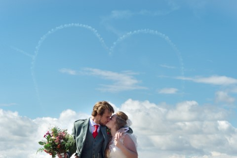 Bride and groom kissing while a plane makes a heart in the sky