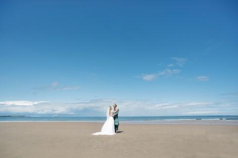 Bride and groom posing on Bellhaven Beach, Dunbar Scotland