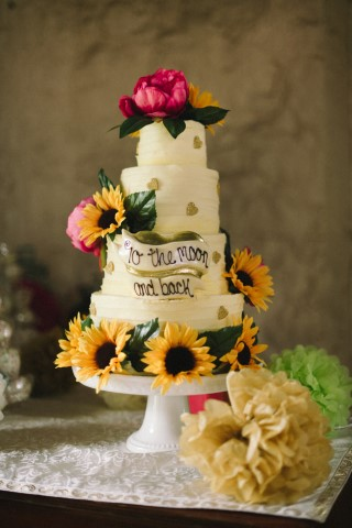 4 tier wedding cake with gold hearts, sun flowers and pink peonies