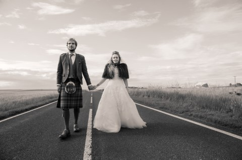 Bride and groom holding hands in the middle of the street captured by Crofts & Kowalczyk Photography