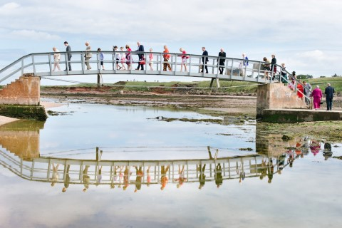 Wedding guests crossing over a bridge in Scotland to get to the wedding ceremony