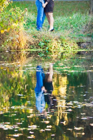 Couple standing in front of a pond for an engagement session captured by Meely Photographer