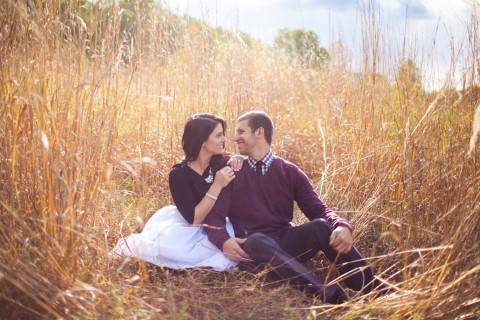 Couple sitting in a field for an engagement session