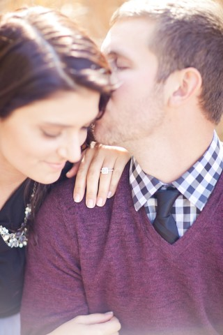 Engaged couple posing for a engagement shoot with women wearing a cushion cut diamond ring