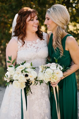 Bride standing with bridesmaid wearing a forest green gown and holding a white bouquet with ribbons