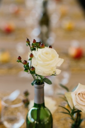 White rose with hypercum berries in a wine bottle for wedding decor