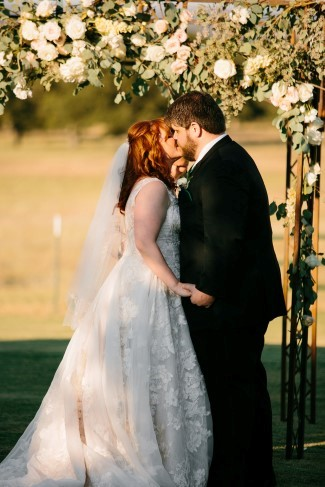 Bride and groom kissing under archway covered in light colored flowers in outdoor wedding