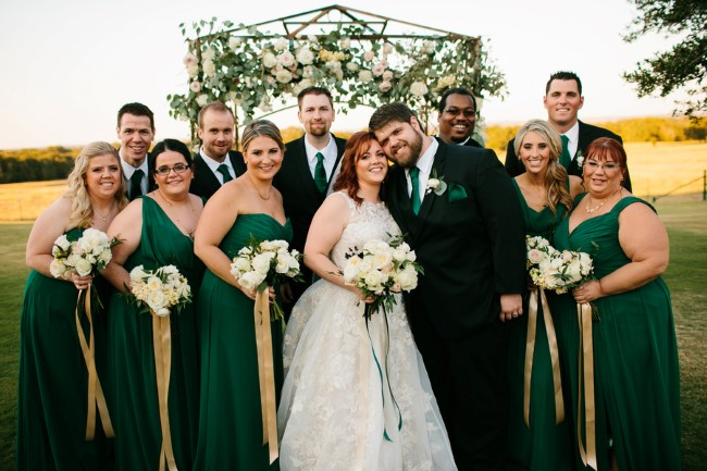 Bride and groom standing with wedding party wearing forest green gowns and ties captured by Rachel Meagan Photography