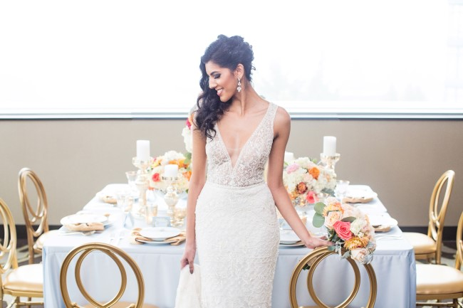 Bride standing in front of gold and blue styled shoot wedding table in Element Hotel