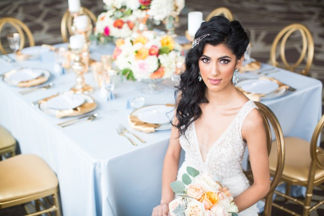 Bride wearing a lace gown sitting in a gold reception chair captured by Denise Lin Photography