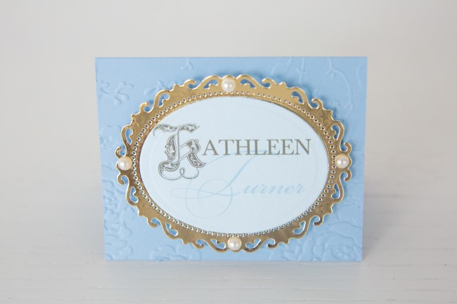 Ornate gold and blue place card for a wedding reception created by Making Memories With Scrapbooking