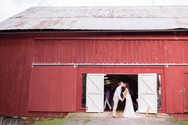 Bride and groom kissing in front of red barn at Genesee Valley