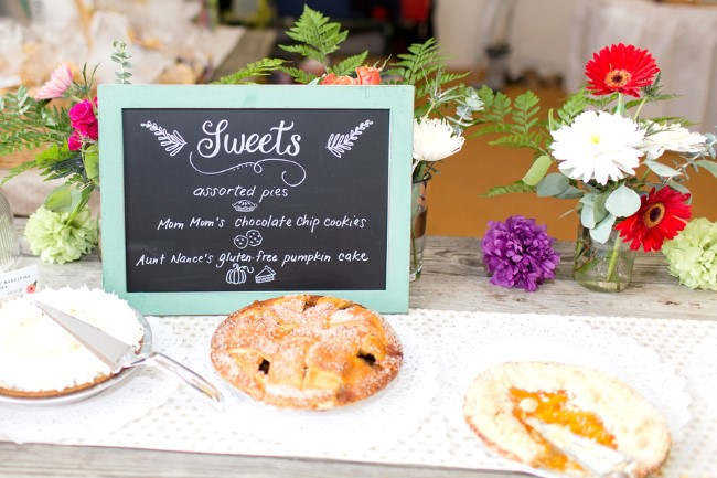 Pie dessert buffet for wedding reception with brightly colored flowers