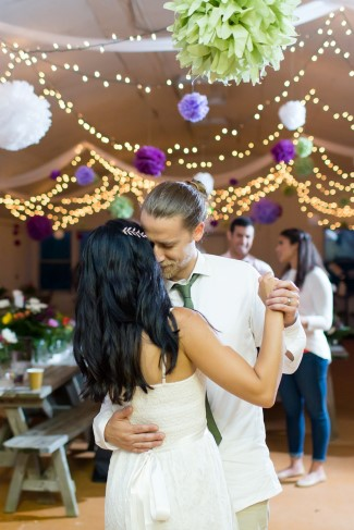 Bride and groom dancing under white light and purple and green paper pom poms
