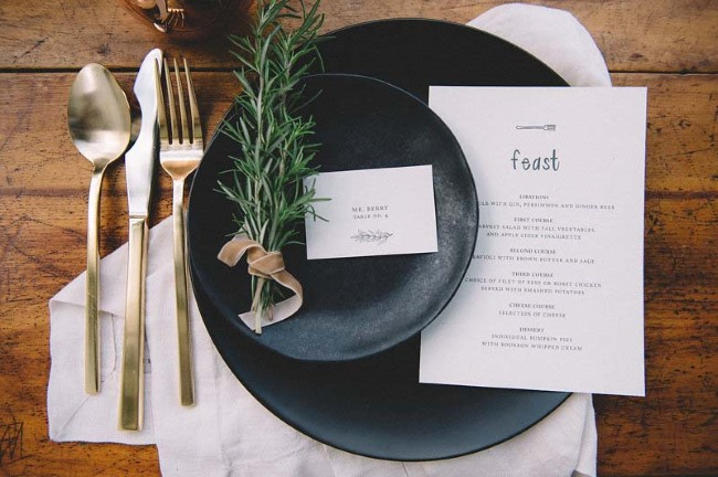 Black plates with gold cuttlery and sprigs of rosemary for wedding reception