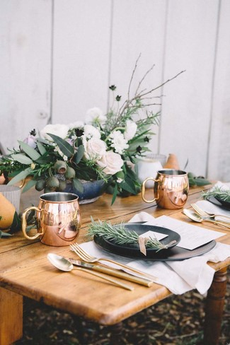 Table scape with black plates and bronze silverware and mugs