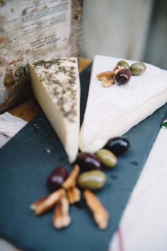Cheese plate on black slate with olives for wedding reception