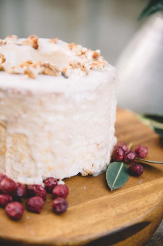 White single tier cake sprinkled with nuts with cranberries