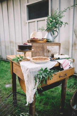 Wedding dessert table decorated with foliage and cheese cloth