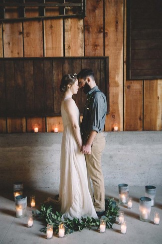 Bride and groom head to head in a circle of foliage surrounded by candles