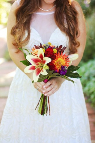Bride carrying a bouquet of lillies and orange flowers created by Alberts Florist