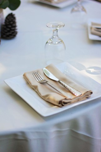 Outdoor wedding reception place setting with gold napkin
