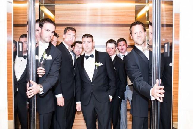 Groom standing in a door way with groomsmen wearing black tuxedos
