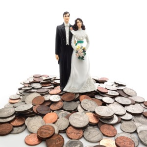 plastic bride and groom on a pile of coins ft