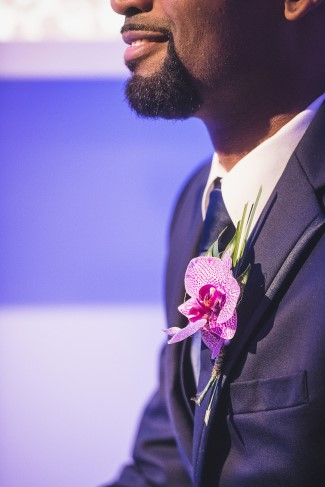 Groom wearing an orchid boutonniere